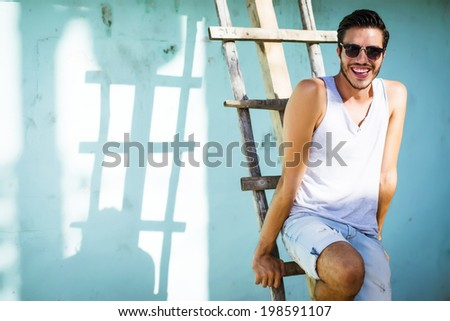 Portrait of a young handsome man, fashion model, with toupee in urban background - stock photo