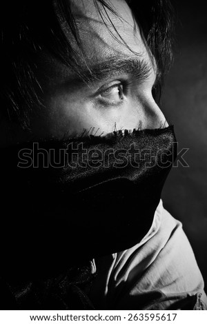 portrait of a young handsome man in a sling on her mouth - stock photo