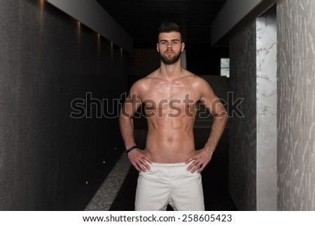Portrait Of A Young Handsome Man In The Modern Corridor Where He Poses - stock photo