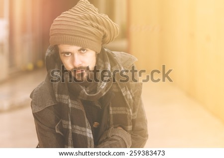 Portrait of a young handsome man in winter time city context warm filter applied - stock photo
