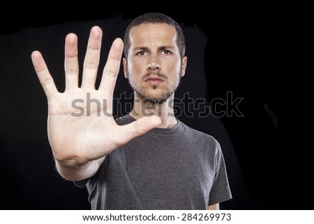 portrait of a young handsome man making stop sign gesture with the hand - stock photo