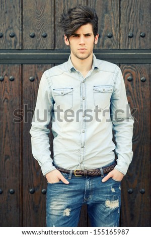 Portrait of a young handsome man, model of fashion, with modern hairstyle in urban background - stock photo