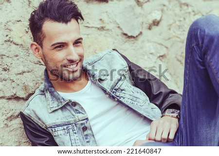 Portrait of a young handsome man, model of fashion, with modern hairstyle smiling in urban background - stock photo