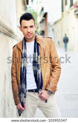 Portrait of a young handsome man, model of fashion, with toupee in urban background - stock photo