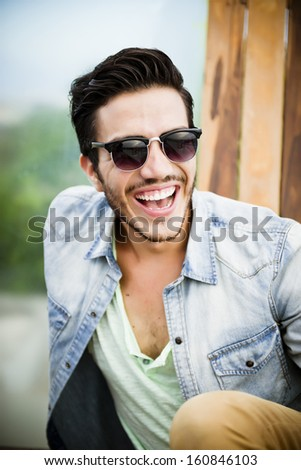 Portrait of a young handsome man,sitting outdoors, with toupee and sunglasses in urban background - stock photo