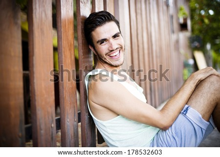 Portrait of a young handsome man,sitting outdoors, with toupee in urban background - stock photo