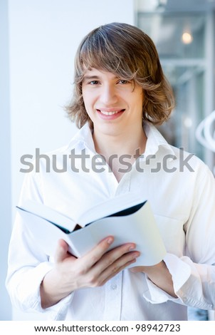 portrait of a young handsome man with a book - stock photo