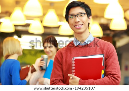 Portrait of a young happy asian man standing in campus - stock photo