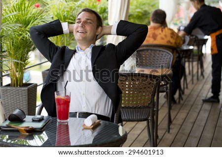 Portrait of a young happy business man in a dark suit and white shirt sitting in summer cafe - stock photo