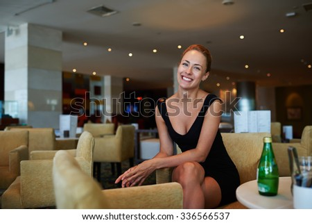 Portrait of a young happy elegant lady dressed in luxury black dress enjoying rest after negotiations, cheerful woman entrepreneur with beautiful smile posing while sitting in modern coffee shop  - stock photo
