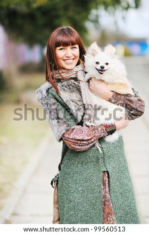 Portrait of a young happy female hugging a cute puppy - stock photo
