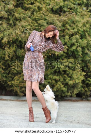 Portrait of a young happy female walking with her puppy - stock photo