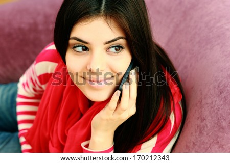 Portrait of a young happy thoughtful woman talking on the phone and looking up - stock photo