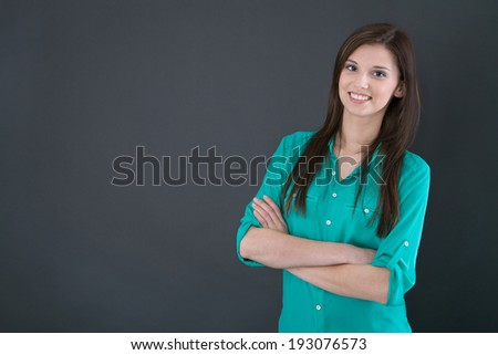 Portrait of a young happy woman isolated on a blackboard. - stock photo