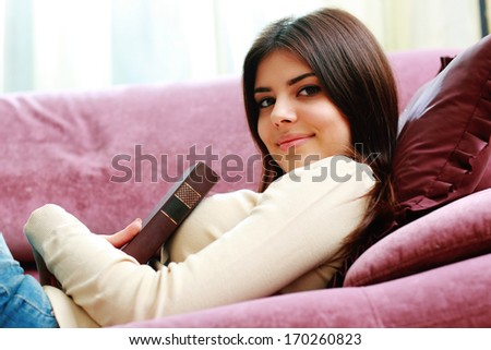 Portrait of a young happy woman lying on the sofa with book at home - stock photo