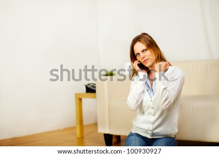 Portrait of a young happy woman speaking at mobile phone while is celebrating a victory - stock photo