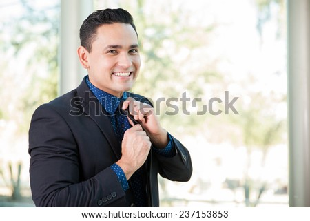 Portrait of a young Hispanic businessman fixing his tie and smiling - stock photo