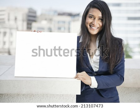 Portrait of a young Indian businesswoman holding Moodboard sign - stock photo