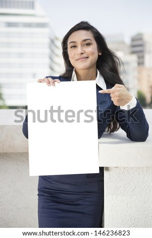 Portrait of a young Indian businesswoman pointing towards sign - stock photo