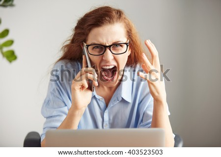 Portrait of a young irritated businesswoman wearing glasses and shirt looking with anger at camera. Headshot of an outraged female boss shouting on cell phone while working on her laptop in office.  - stock photo