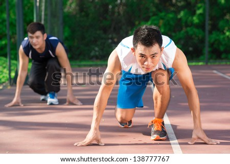 Portrait of a young jogger ready to run on the foreground - stock photo
