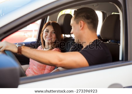 Portrait of a young Latin couple sitting on a car and having a good time during their trip - stock photo