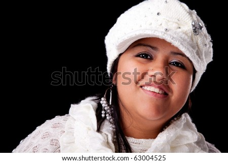 Portrait of a young latin woman smiling, in autumn/winter clothes, isolated on black. Studio shot - stock photo