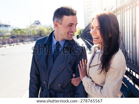 Portrait of a young laughing couple walking outdoors - stock photo
