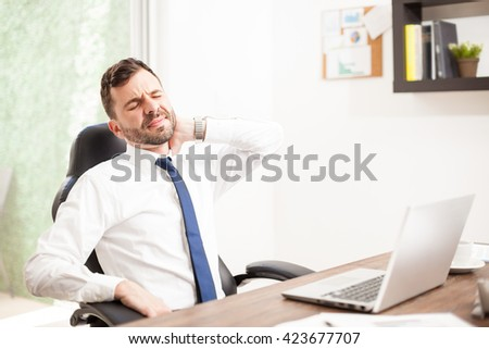 Portrait of a young lawyer with a beard suffering from neck pain in the office due to a bad sitting posture - stock photo