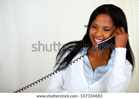 Portrait of a young lovely female laughing and conversing on phone - stock photo