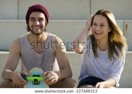 Portrait of a young, lovely, happy skateboarding couple on concrete steps on a bright, summer afternoon, with a pleasant, friendly atmosphere. - stock photo