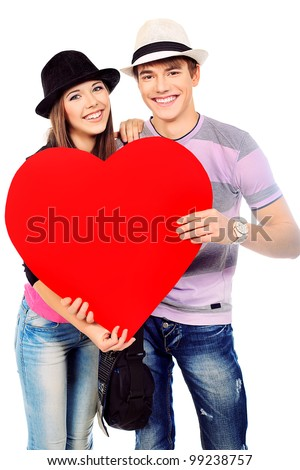 Portrait of a young loving couple holding big heart. Isolated over white. - stock photo