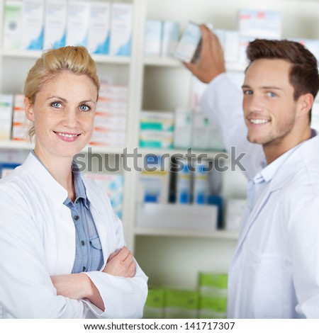 Portrait of a young male and female pharmacists smiling in front of medicines at drugstore - stock photo