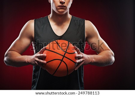 Portrait of a young male basketball player gripping the ball tightly on red background - stock photo