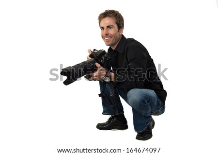 Portrait of a young male photographer with a professional camera, crouching down, getting ready to take pictures. - stock photo