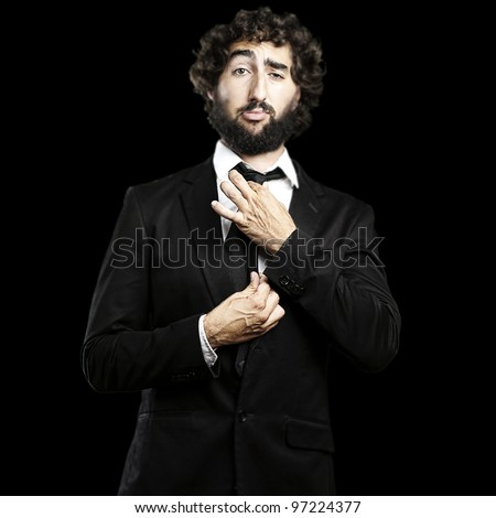portrait of a young man adjusting his suit against a black background - stock photo