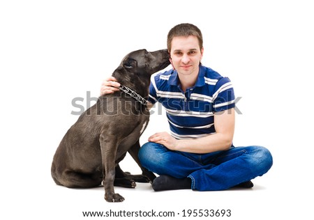 Portrait of a young man and his dog that licks - stock photo