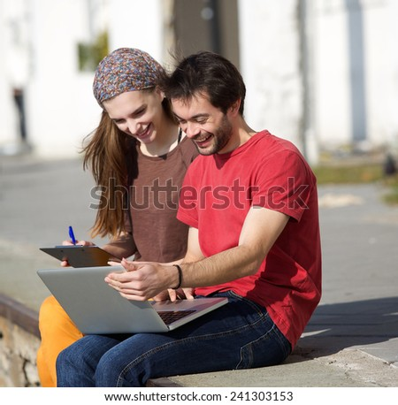 Portrait of a young man and woman smiling at laptop outdoors  - stock photo