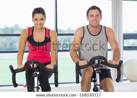 Portrait of a young man and woman working out at class in gym - stock photo