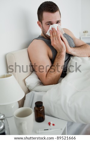 Portrait of a young man blowing his nose in his bedroom - stock photo