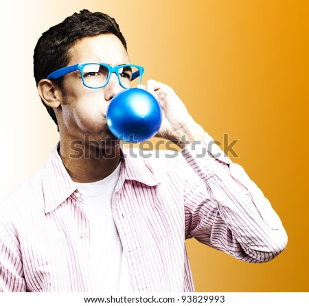 portrait of a young man blowing up a blue balloon against an orange background - stock photo