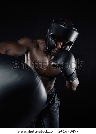 Portrait of a young man boxer throwing a punch at camera while practicing on black background. Male athlete wearing boxing gloves exercising boxing. - stock photo