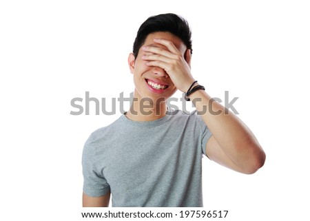Portrait of a young man covering his eyes with his hand over white background - stock photo