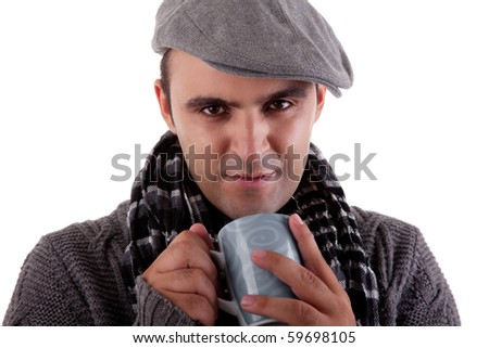 Portrait of a young man, drinking a hot drink in autumn/winter clothes, isolated on white. Studio shot - stock photo
