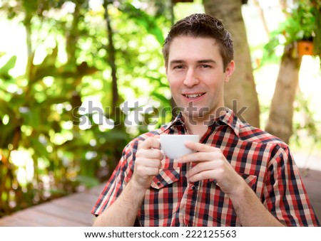 Portrait of a young man drinking coffee - stock photo