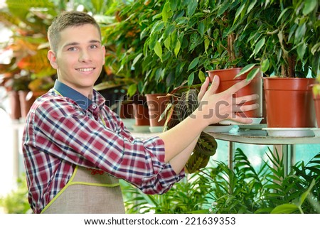 Portrait of a young man florist that cares for the flowers in the greenhouse - stock photo