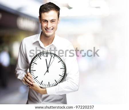 portrait of a young man holding a clock at a crowded place - stock photo