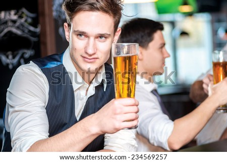 Portrait of a young man holding a glass of beer. Three cheerful friends met at the bar and drink a beer while the bartender is standing on the bar. Friends having fun together - stock photo