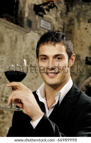 Portrait of a young man holding a glass of red wine - stock photo