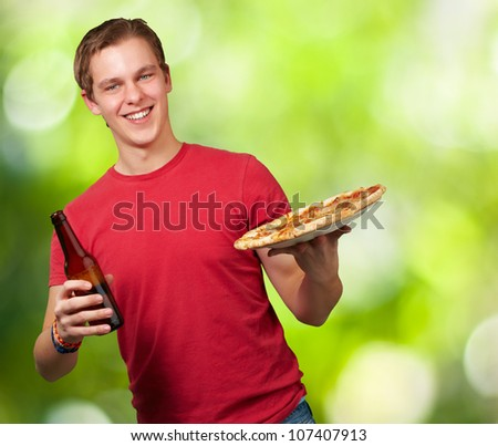 portrait of a young man holding a pizza and a beer against a nature background - stock photo